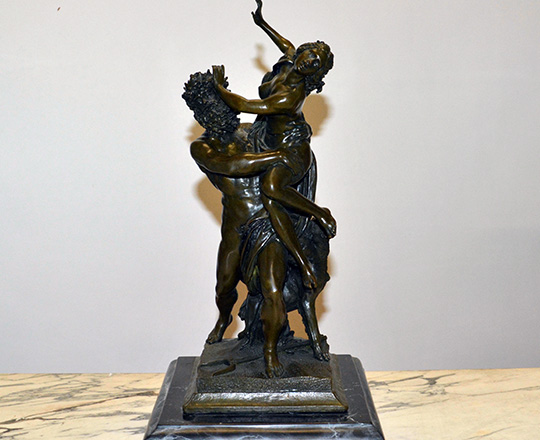 Lot 386: Dark medal color bronze statue of woman captured by faun. H 38 cm.