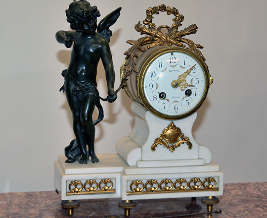 Lot 410: 19th c Louis XVI white marble mantle clock with bronze statue of Cupid beside mouvement by Butneau,Autun. H31cm.