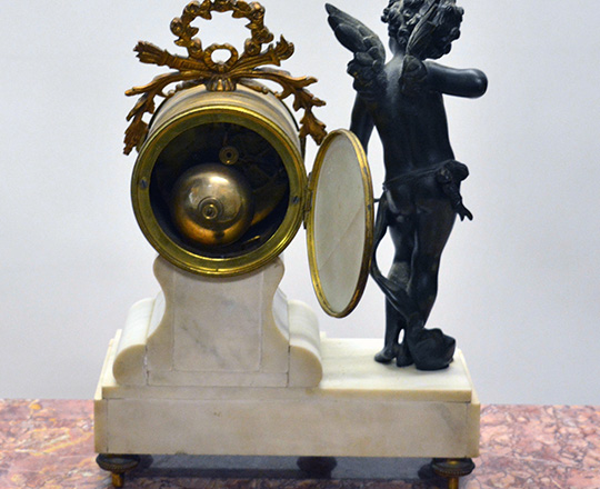 Lot 410_1: 19th c Louis XVI white marble mantle clock with bronze statue of Cupid beside mouvement by Butneau,Autun. H31cm.