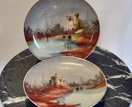 Lot 432: Pair early cent Montigny hand painted plates with caste by countryside scene. Dia 28cm.