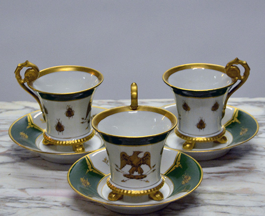 Lot 479: Three gilt rimmed cups & saucers with Empire eagle & bee emblem ( symbols that replaced the monarch lily flower).